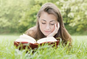 Portrait of happy student relaxed outdoors reading book.; Shutterstock ID 77215492; PO: test; Job: dev; Client: drone